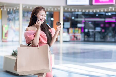 Asian Women are shopping In the summer she is using a credit card using a smart phone and smiling while standing outdoors and enjoys shopping.