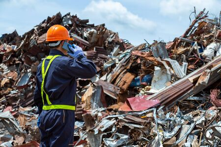 workers in landfill dumping, Garbage engineer, recycling, wearing a safety suit standing in the outdoor recycling center have a metal scrap pile in the background. Banco de Imagens