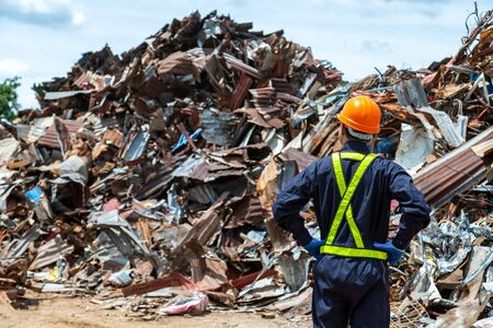 workers in landfill dumping, Garbage engineer, recycling, wearing a safety suit standing in the outdoor recycling center have a metal scrap pile in the background. Stock Photo