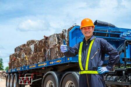workers in landfill dumping, Garbage engineer, recycling, wearing a safety suit Standing in front of the truck, the concept for the safety of the recycling industry. Stock Photo
