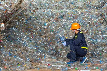 workers in landfill dumping, Check the plastic bottles in the recycling plant. Stock Photo
