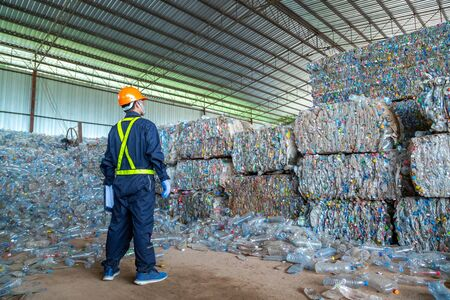 workers in landfill dumping, Garbage engineer, recycling, wearing a safety suit standing in the recycling center have a plastic bottle for recycling in the factory.