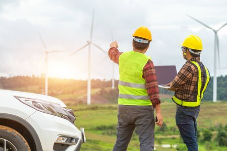Two Windmill engineer inspection and progress check wind turbine at construction site By using a car as a vehicle. Banco de Imagens