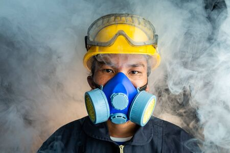 A rescue worker wears a respirator in a smokey, toxic atmosphere. Image show the importance of protection readiness and safety in industrial factory.
