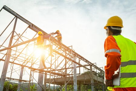 A construction worker control in the construction of roof structures on construction site and sunset background Фото со стока