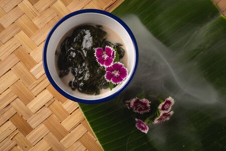Thai dessert, Icevine, Pareira barva with coconut milk on wooden table, Top view
