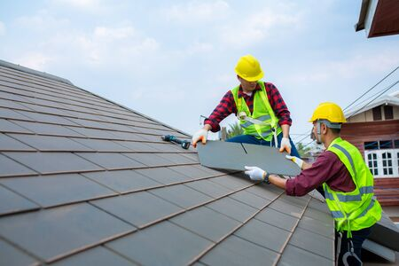 Two construction workers helped to Fixing roof tiles, turning the gray in the house with the blue sky in the safety suit for safety. Stok Fotoğraf