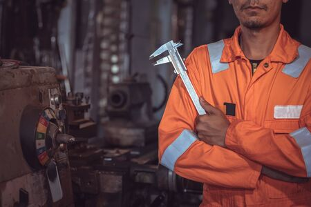 Close-up Industrial Workers, wearing safety clothing, using vernier calipers, measuring instruments, controlling objects working in industrial plants, shop, lathe shop