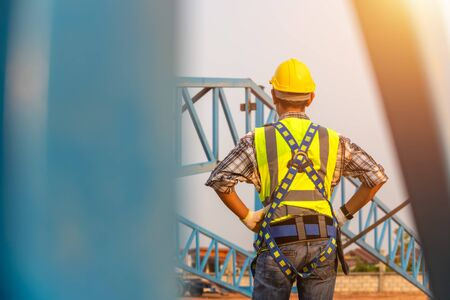[safety body construction] Engineer working in a metal roof structure, Construction engineer wear safety uniform at height equipment inspection metal roofing work for industrial. Zdjęcie Seryjne