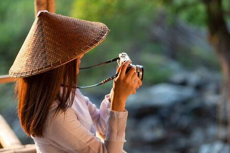 Vietnamese girl in traditional costume holding a film camera in the midst of nature Stock fotó