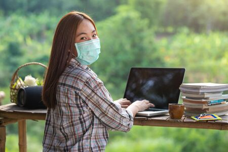 Happy relaxed asian young woman sitting and working on a laptop in the midst of nature wearing medical face mask and look at the camera to prevent the spread of the corona virus. Stock fotó