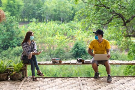 Asian woman and man in social distancing sitting on bench in the middle of nature, Social distancing concept. Stock fotó