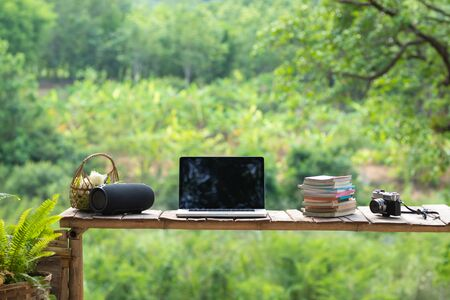 laptop and film camera with books on wooden table with beautiful green tree background.
