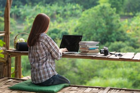 Happy relaxed asian young woman sitting and working on a laptop in the midst of nature.