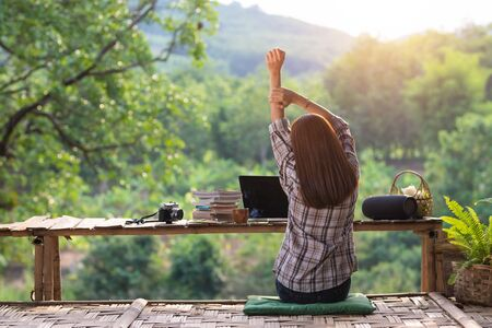 Happy relaxed asian young woman sitting in the midst of nature with a laptop in the back of her stretching her arms above her head and looking out of the nature in the morning. Stock fotó