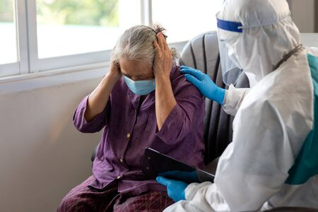 Asian doctor wear PPE suit talk with old female patient about disease symptom, elderly health check up , they wear surgical mask with Providing comfort and encouragement for the elderly.