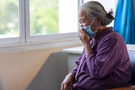 Senior asian woman wearing face mask during corona virus and flu outbreak. Disease and illness protection. the aging female patient that is at risk for infection corona virus [covid-19]. Stock fotó