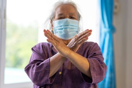 Senior asian woman wearing face mask during corona virus and flu outbreak. Disease and illness protection. show stop hands gesture for stop corona virus outbreak. Stock fotó