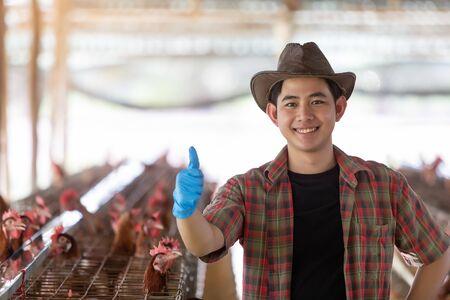 Portrait of young asian man farmer in Eggs chicken farm.