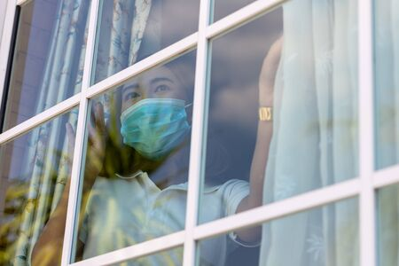 Coronavirus. Sick woman of corona virus looking through the window and wearing mask protection and recovery from the illness in home. Quarantine. Patient isolated to prevent infection. new normal.