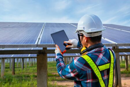 Asian engineer working on checking equipment in solar power plant, Pure energy, Renewable energy