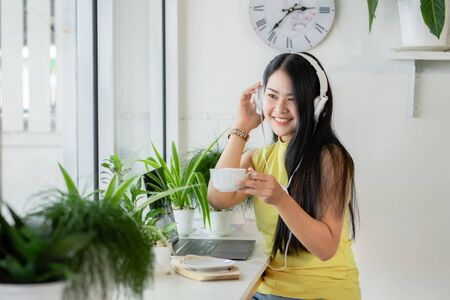 Asian smiling girl student wear wireless headphone study online with skype teacher in a coffee shop, woman learn language listen lecture watch at laptop sit in cafe, distant education, New normal
