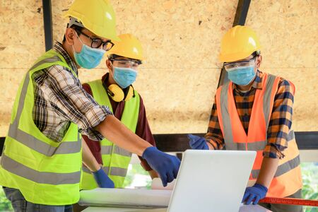 Team of construction engineers and three architects are ready to wear medical masks. Coronavirus or Covid-19 wear masks during the design of construction. New normal Foto de archivo