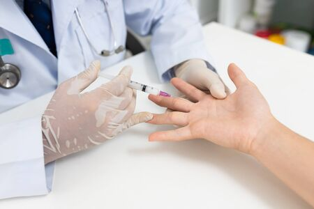 Asian doctor or nurse hands with syringe injecting to palm medical. Carpal tunnel syndrome, arthritis, neurological disease concept. Numbness of the hand
