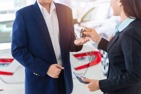 Asian auto business, car sale, deal, gesture and people concept - close up of dealer giving key to new owner in auto showroom