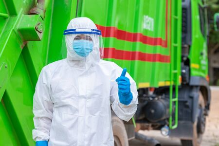 Asian worker double like and tumb and upwear PPE protective clothing against corona virus of Infectious waste garbage collector truck loading waste.