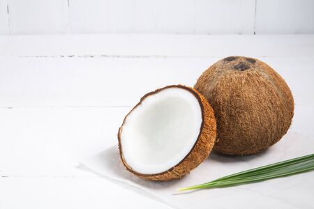 Coconut with half and leaves on white wood background Imagens