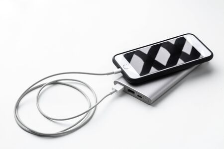 Smartphone charging with power bank on white background.