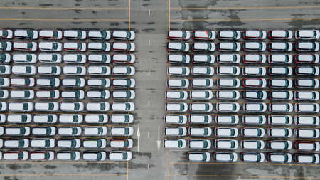 Aerial view new car lined up in the port for import and export business logistic to dealership for sale, Automobile and automotive car parking lot for commercial business car industry.
