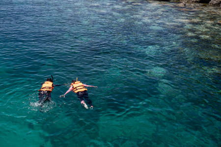 Two people snorkeling wear a life jacket over coral reef with clear blue ocean water in tropical clear sea