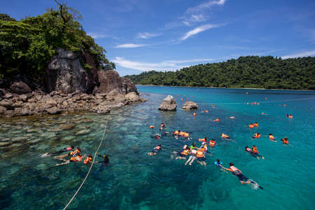 Tourist group snorkeling wear a life jacket over coral reef with clear blue ocean water in tropical clear sea