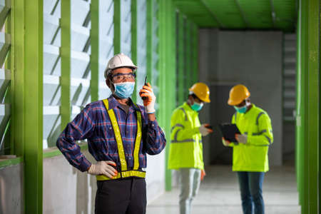 Asian worker under inspection and checking production process on factory station by wearing safety mask to protect for pollution and virus in the factory