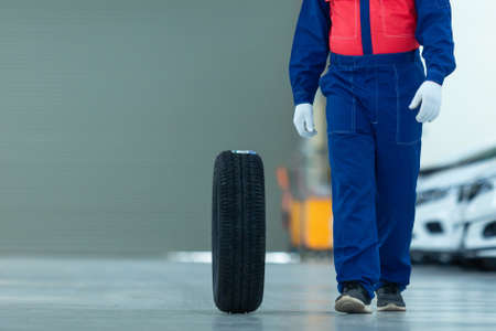 Auto mechanic change tire attractive auto mechanic man in blue uniform with blue gloves rolling wheel going on the autoservice in the auto repair center