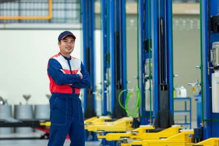 Asian man auto mechanic in auto repair service center black ground is a car lift.