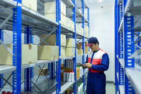 Asian worker on a automotive spare parts warehouse checking products