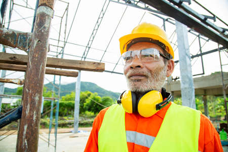 Asian senior worker engineer wearing helmet and safety clothes in the house construction site. Working elderly people concept 版權商用圖片