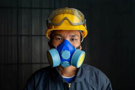 Asian worker wear wears a respirator in a smokey, toxic atmosphere. Image show the importance of protection readiness and safety in industrial factory. 版權商用圖片