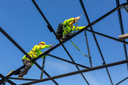 Safety height equipment in the construction site; Asian worker wear safety height equipment to install the roof. Fall arrestor device for worker with hooks for safety body harness. Zdjęcie Seryjne