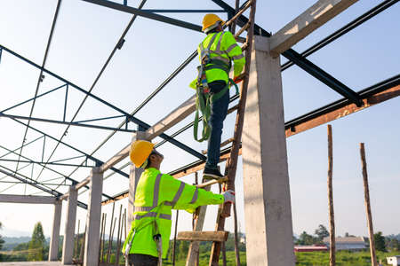 Safety height equipment in the construction site; Asian worker wear safety height equipment to install the roof. Fall arrestor device for worker with hooks for safety body harness. 版權商用圖片