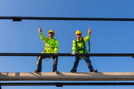 Safety height equipment in the construction site; Asian worker wear safety height equipment to install the roof. Fall arrestor device for worker with hooks for safety body harness.