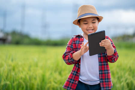 Asian Little boy watching tablet and interested in learning the surroundings in the green fields, education concept outside the classroom Educational freedom