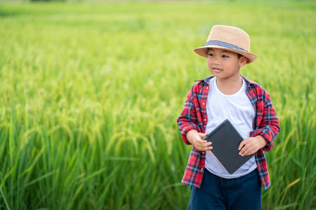Happy Asian Little boy with a tablet interested in learning the surroundings in the green fields, education concept outside the classroom Educational freedom  In the age of technology