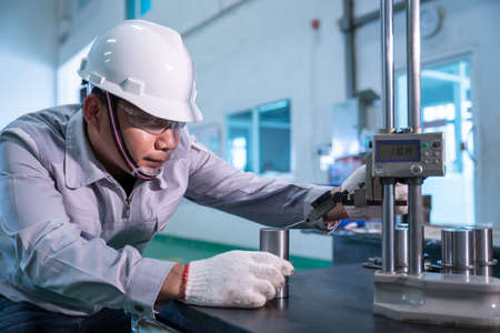 Asian technician worker wearing a safety suit and Quality Checking with hight gauge mass Product on Granite Surface Plate in industrial factory.