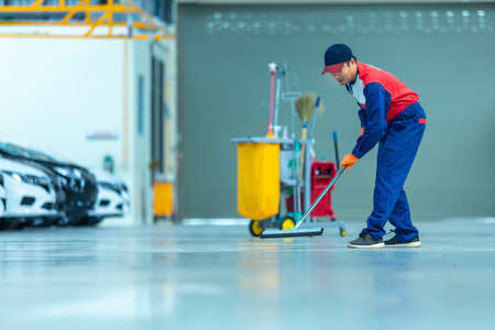 Asian worker in car mechanic repair service center cleaning using mops to roll water from the epoxy floor. Mops in the car repair service center. Foto de archivo