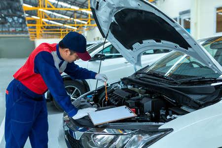 Auto mechanic checking car engine oil in car auto repair service center. Standard-Bild