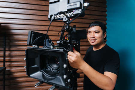 Asian photographer with a movie camera in the filming set. Archivio Fotografico